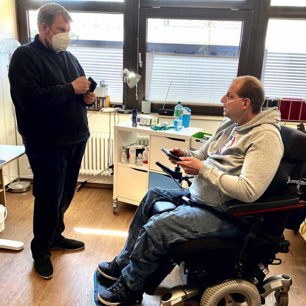 Auf dem Bild ist Dirk Lehmann zu sehen der Patrick, einem Bewohner etwas über Alexa erzählt